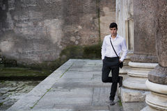 Handsome young man outdoor next to ancient marble columns Royalty Free Stock Images