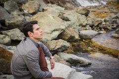 Handsome young man outdoor sitting alone at river or water stream Royalty Free Stock Photos