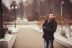 Handsome young man outdoor in winter coat. Handsome young man outdoor in winter fashion, wearing coat and woolen scarf in city park Royalty Free Stock Photos