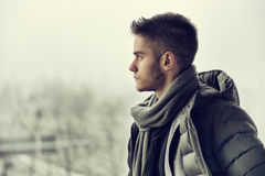 Handsome young man outdoor in winter. Profile view of handsome young man outdoor in winter wearing scarf, looking away thinking Royalty Free Stock Photos