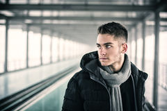 Handsome young man outdoor in winter. Profile view of handsome young man outdoor in winter wearing scarf, looking away thinking Stock Photography