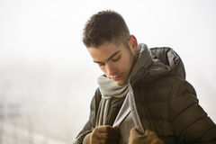 Handsome young man outdoor in winter. Profile view of handsome young man outdoor in winter wearing scarf, looking away thinking Stock Photos