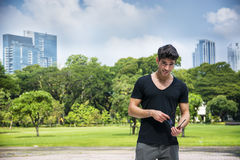 Handsome young man outdoors in city park. Handsome friendly young man outdoors in city park in Bangkok, Thailand, in front of small lake or water pond,looking at stock photos