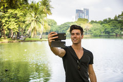 Handsome young man outdoors in city park. Handsome friendly young man outdoors in city park taking selfie photo with smartphone camera, in Bangkok, Thailand, in royalty free stock image