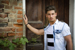Handsome young man outdoors in front of old house. 's entrance door, looking at camera royalty free stock image
