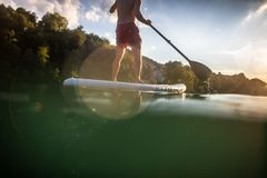 Handsome young man on a paddle board. Getting a great exercise on a lovely river in warm evening sunlight stock photo