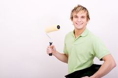 Handsome young man painting house. A smiling handsome young man painting house with roller brush Stock Photo
