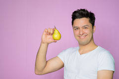 Handsome young man with a pear Stock Photography