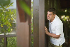 Handsome young man peeking, looking for something close to windo. W royalty free stock images