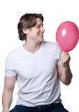 Handsome young man with a pink  balloon Stock Photos