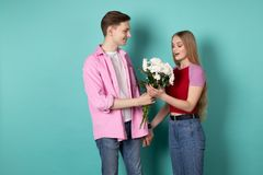 Handsome young man in pink shirt gives a bouquet of white flowers to his beautiful blonde girlfriend stock images