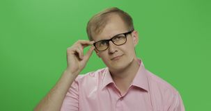 Handsome young man in the pink shirt and glasses looking in the camera royalty free stock photo