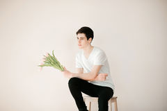 Handsome young man with pink tulips Royalty Free Stock Image