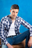 Handsome young man with plaid shirt on blue Stock Photography