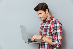 Handsome young man in plaid shirt using laptop Stock Photos