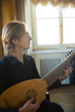Handsome young man playing antique lute Royalty Free Stock Photos