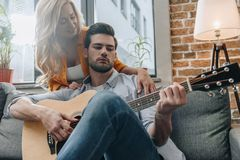 Handsome young man playing guitar for girlfriend. At home royalty free stock photo