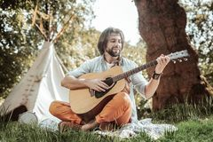 Handsome young man playing guitar near tent