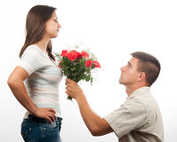 Handsome young man pleading for forgiveness. Handsome young men pleading for forgiveness and offering bouquet of roses to his girlfriend royalty free stock photography