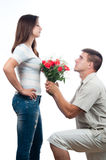 Handsome young man pleading for forgiveness. Handsome young men pleading for forgiveness and offering bouquet of roses to his girlfriend stock image