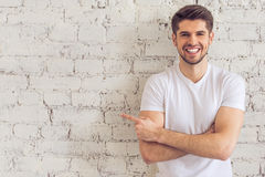 Handsome young man. Is pointing away, looking at camera and smiling, standing against white brick wall Royalty Free Stock Images