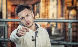 Handsome young man pointing fingers at you. Towards the camera, with confident look royalty free stock images