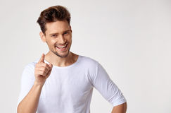 Handsome young man pointing something. Handsome young guy pointing something Stock Images