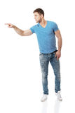 Handsome young man pointing up. Stock Photography