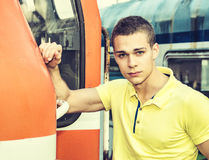 Handsome young man in polo shirt in front of train Royalty Free Stock Photo
