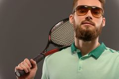 Handsome young man in polo shirt holding tennis Stock Images
