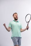 Handsome young man in polo shirt holding tennis Stock Photos