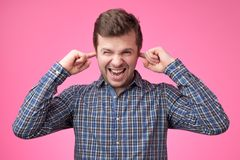 Handsome young man portrait with fingers in ear not listening expression stock photo