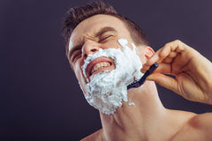Handsome young man. Portrait of handsome man getting hurt while shaving with a razor, on a dark background Stock Photo