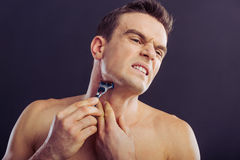 Handsome young man. Portrait of handsome naked man getting hurt while shaving with a razor, on a dark background Royalty Free Stock Photo