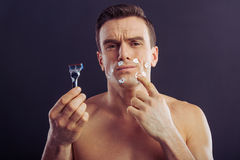 Handsome young man. Portrait of handsome naked man holding a razor and pointing on little cuts on his face, on a dark background Royalty Free Stock Photo