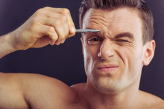 Handsome young man. Portrait of handsome naked man plucking his eyebrows, on a dark background stock photo