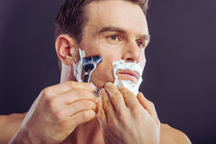 Handsome young man. Portrait of handsome naked man shaving using a razor and looking away, on a dark background Royalty Free Stock Photo