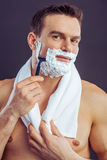 Handsome young man. Portrait of handsome naked man with a towel on his shoulders shaving using a razor and looking at camera, on a dark background Stock Image