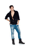 Handsome young man posing. Handsome young fashion model standing and wearing jeans, boots and a black jacket.  on white background. Studio vertical image Royalty Free Stock Photo