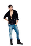 Handsome young man posing. Handsome young fashion model standing and wearing jeans, boots and a black jacket.  on white background. Studio vertical image Royalty Free Stock Image