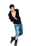 Handsome young man posing. Handsome happy young fashion model posing wearing jeans, boots and a black jacket.  on white background. Studio vertical image Royalty Free Stock Photos