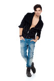 Handsome young man posing. Handsome young fashion model standing with hands in pockets, wearing jeans, boots and a black jacket.  on white background. Studio Royalty Free Stock Images