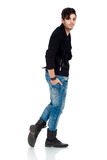 Handsome young man posing. Handsome young fashion model wearing jeans, boots and a black jacket.  on white background. Studio vertical image Stock Photography