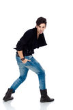 Handsome young man posing. Handsome young fashion model wearing jeans, boots and a black jacket.  on white background. Studio vertical image Stock Photos