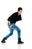 Handsome young man posing. Handsome happy young fashion model wearing jeans, boots and a black jacket.  on white background. Studio vertical image Royalty Free Stock Photo