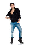 Handsome young man posing. Sexy young fashion model wearing jeans, boots and a black jacket.  on white background. Studio vertical image Royalty Free Stock Image