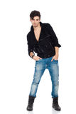 Handsome young man posing. Attractive young fashion model wearing jeans, boots and a black jacket.  on white background. Studio vertical image Royalty Free Stock Photography