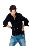 Handsome young man posing. Confident young fashion model wearing jeans, boots and a black jacket. Isolated on white background. Studio vertical image Royalty Free Stock Photos