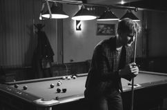Handsome young man posing with billiard cue. Black and white photo. man rested his head in the cue Royalty Free Stock Photography