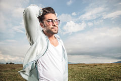 Handsome young man posing while fixing his hair. Stock Image